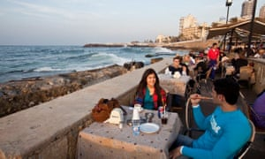 A young couple enjoy a sheesha at a seafront cafe.