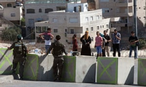 Palestinian residents of the east Jerusalem neighbourhood of Issawiya wait to pass an Israeli checkpoint on Friday, one of a number to have been set up around the city at the government's instruction.