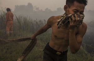 A firefighter holds a water pipe as they extinguish a fire on burned peatland and fields in Palembang, South Sumatra, Indonesia. The air pollution or haze has been an annual problem for the past 18 years in Indonesia. It's caused by the illegal burning of forest and peat fires on the islands of Sumatra and Borneo to clear new land for the production of pulp, paper and palm oil. Singapore and Malaysia have offered to help the Indonesian government to fight against the fires, as infants and their mothers are evacuated to escape the record pollution levels.