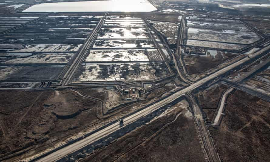 Trucks and machinery along routes within the Suncore Oil Sands site near to Fort McMurray in Northern Alberta. Canada's tar sands is one of the largest industrial projects on the planet, turning boreal forest, rivers and bogs into a scarred landscape.
