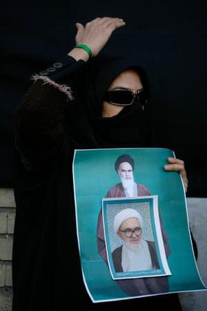 绿色运动的支持者哀悼伊朗改革运动的精神之父大阿亚图拉蒙塔泽里的死亡,在海报上贴上了更大的阿亚图拉霍梅尼。在库姆市,她捂住脸以避免被安全人员识别。