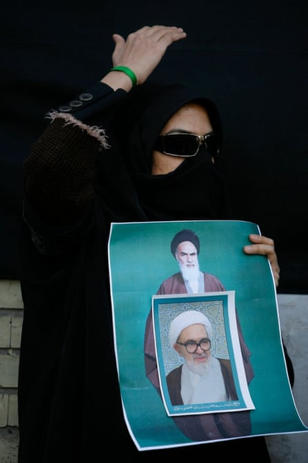 A supporter of the Green Movement mourns the death of Grand Ayatollah Montazeri, the spiritual father of Iran's reform movement, shown in a poster pasted over a larger one of Ayatollah Khomeini. She covers her face to avoid identification by security, in the city of Qom.