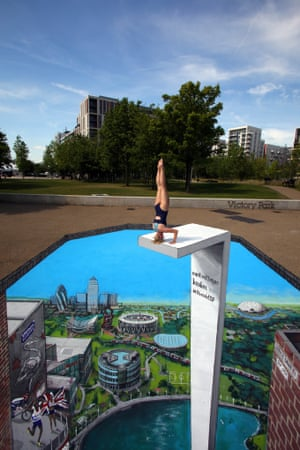 Swimmer Tegan Jolly prepares to 'dive' into a piece of 3D artwork depicting scenery from east London, the Queen Elizabeth II Olympic Park and cameos from London 2012, which has been created by artists 3D Joe and Max, at the East Village in London.
