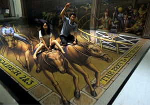 Visitors pose for photos on 3D Pavement Art 3D Art Painting Exhibition by Kurt Wenner, Indonesia, Jakarta - 16 Dec 2013 The painting made by U.S. artist Kurt Wenner is on display at Artphoria 2013 exhibition at the Ciputra Artpenuer Center.