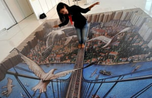 A visitor poses for photos on 3D Pavement Art 3D Art Painting Exhibition by Kurt Wenner, Indonesia, Jakarta - 16 Dec 2013 The painting made by U.S. artist Kurt Wenner is on display at Artphoria 2013 exhibition at the Ciputra Artpenuer.