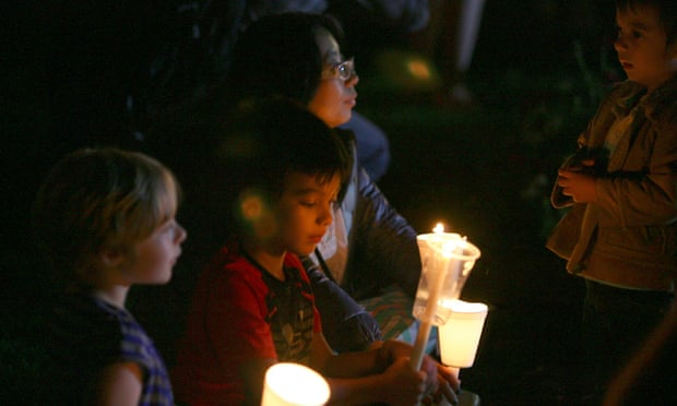 Attendees of the candle light prayer vigil hold their candles up in solidarity during the candlelight prayer vigil at Stewart Park