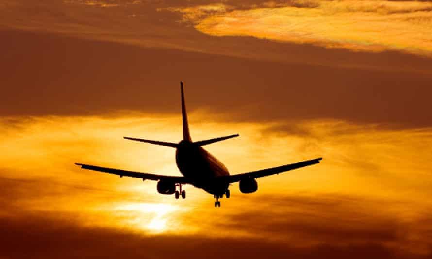 Plane landing, set against the sunset.