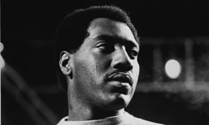 A black and white photo of Otis Redding on stage, the image cropped to his head and shoulders, his head turned slightly so that the stage lighting highlights one side of his face.