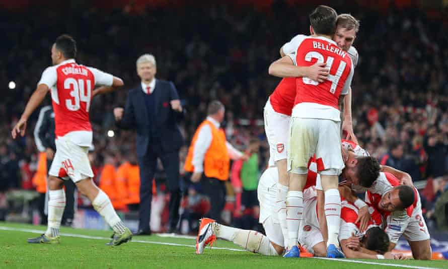 Arsenal's Mesut Özil is mobbed by team-mates after scoring their second goal against Bayern Munich in their Champions League match.