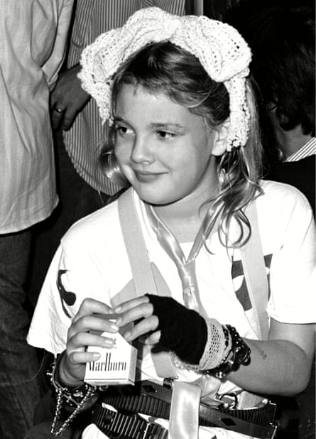 A young Drew Barrymore holding a packet of cigarettes