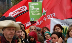Environmental activists hold placards and banners during a march in Brussels ahead of the Paris  conference on climate change to be held in December in Paris.