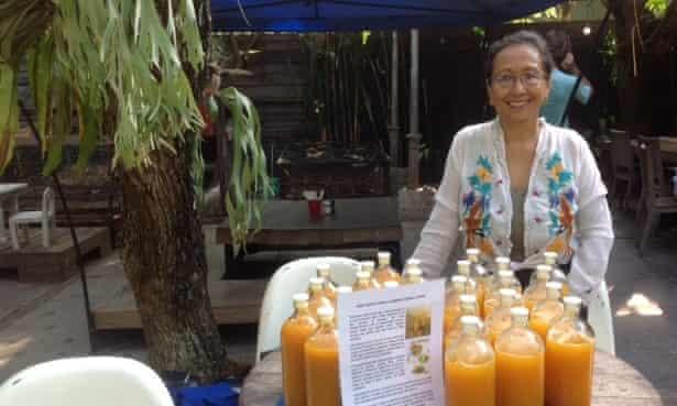 Dotty Chard with her bottles of jamu kunyit asam, a tonic made from turmeric, at the Samadi Sunday market in Canggu, Bali.