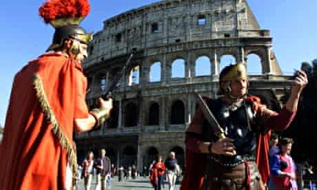 Men dressed as gladiators pose for tourists in front of the Colosseum in Rome