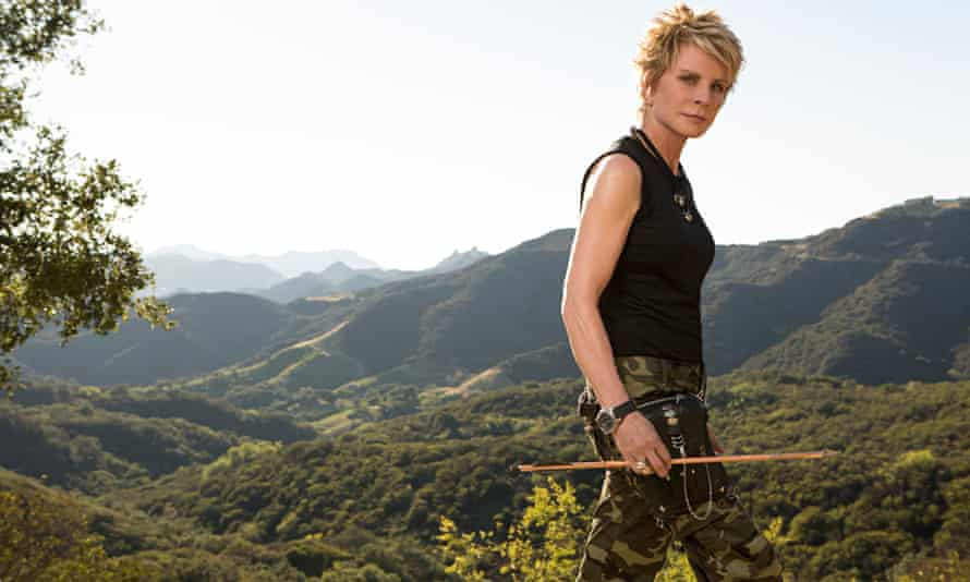 Patricia Cornwell in camoflage trousers walking, carrying an arrow, mountains behind her