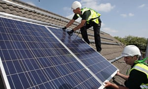 Workmen install solar panels on to the roofs of homes in Delabole