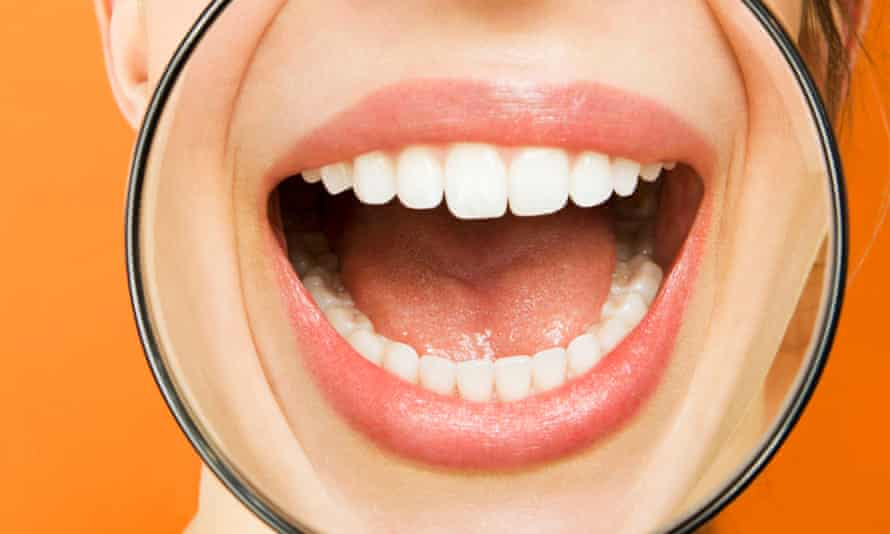 Health feature: Examining the growing body of evidence about mouth-body association, ie how dental issues can affect more than just our oral health and possibly cause cancer, diabetes and other serious illnesses (web and print)Young woman putting magnifying glass over mouth and laughing, portrait