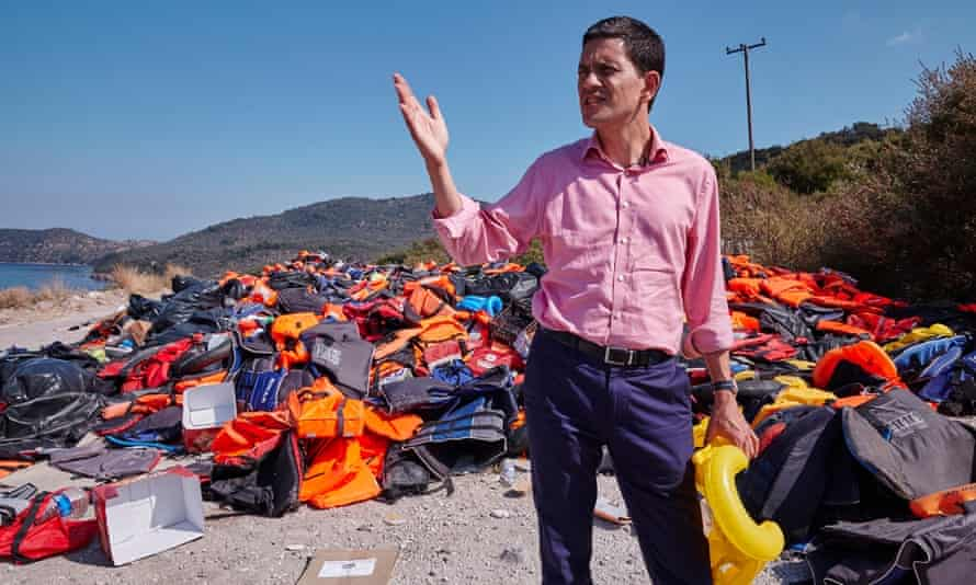 David Miliband in front of a pile of discarded life vests in Lesbos.