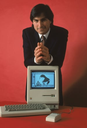 Jobs leans with the Macintosh 128K, the original Macintosh personal computer, 1984.