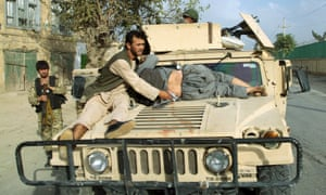 A military vehicle transports a civilian injured in fighting between the Taliban and government forces over control of Kunduz.