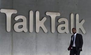 Man walks past Talk Talk sign