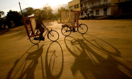 Two cyclists carrying furniture make their way through the streets of Kasese in western Uganda