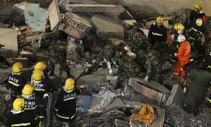 Rescuers search among debris after a building collapsed in Wuyang county, Henan province, China.