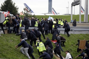 Protesters run up a hill at the Air France headquarters