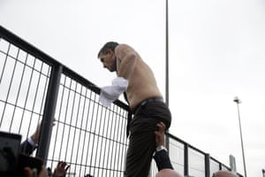 Broseta clambers over a gate after having his shirt torn off his back