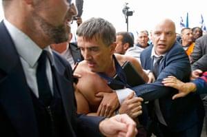 A shirtless Xavier Broseta is evacuated by security