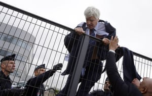 Plissonnier climbs over a fence with the help of police officers