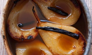 Four baked pear halves, with vanilla pods on top, sitting in syrup