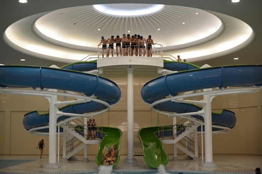 North Korean students ride down a water slide into a swimming pool at Kim Il-Sung University in Pyongyang on 11 April, 2012.