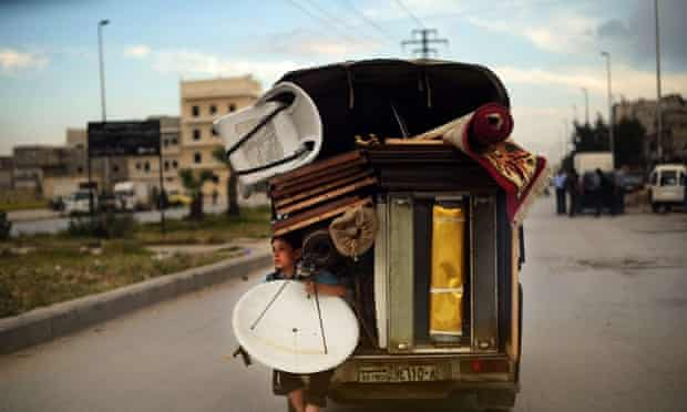 A Syrian boy holds a satellite antenna as he travels on the back of a truck in the northern Syrian city of Aleppo on April 15, 2013.