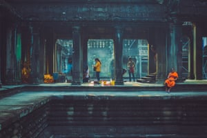 A lone monk, using his mobile phone, sits amid the temple of Angkor Wat, while visitors around him make offerings to Buddha.