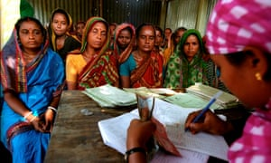 Women in India sit around a desk as another woman counts money