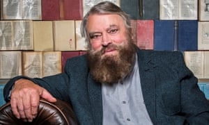 Bearded actor Brian Blessed in front of a wall of opened books