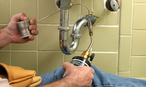 A plumber using a welding torch to solder pipe in the bathroom