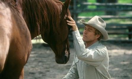 Robert Redford kneeling, his face close to a horse's