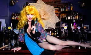 Co-founder of east London gay pub, The Glory, John Sizzle in drag costume lies along the pub bar.