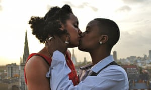 A publicity image for the feminist collective Club des Femmes of two women kissing, in the background is the London skyline.