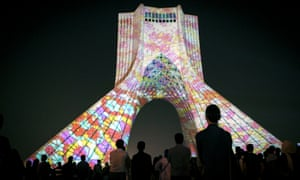 "People watch the light installation on Azadi tower in Tehran, Iran. The German artist Philipp Geist developed light installation made of coloured words and concepts in different languages titled ""Gate of Words"" at the Azadi tower, a symbol of Tehran, over the past three nights to visualise the topics of freedom, peace, space, and time artistically."