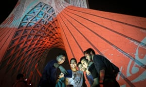 Iranian boys take a selfie as they stand beside the light installation on Azadi tower in Tehran.