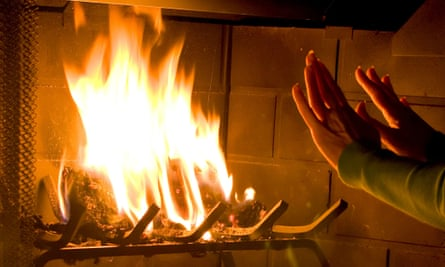 A woman warming her hands by a roaring fire