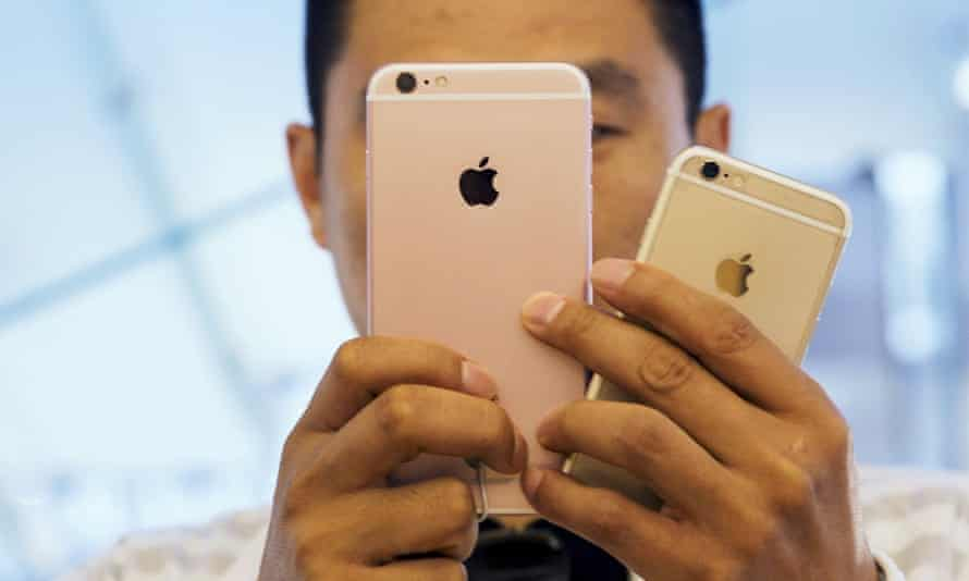 A man takes pictures as Apple iPhone 6s and 6s Plus go on sale at an Apple Store in Beijing, China.