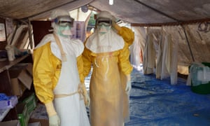 Medical staff of Medecins Sans Frontieres (Doctors Without Borders) put on their protective suits as they stand in a tent of the MSF Donka treatment centre in Conakry.