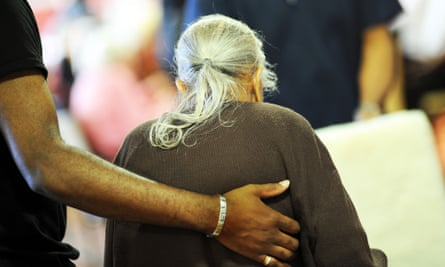 An elderly lady is helped to her chair in a multicultural extra care home Bradford, West Yorkshire.