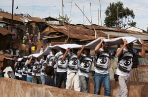 A team pictured installing part of the Women Are Heroes series on the rooftops in Kibera, Kenya in 2009