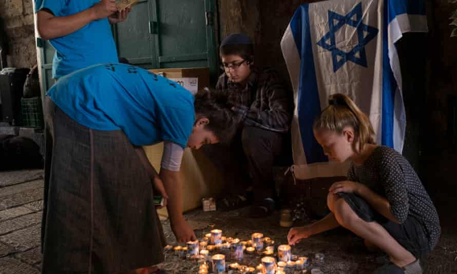 Children pray and light candles at the site of rabbi Nechamia Lavie's killing