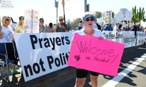 Dulcie Bagley, a supporter of Obama's visit, walks past protesters lining the street in front of the Roseburg regional Airport on Friday.