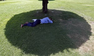 A man sleeps under the shade of a tree during a May 2015 heat wave in New Delhi, India.